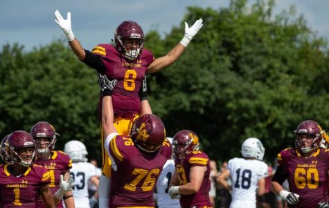 Senior Christo Kelly lifts of senior Trevor Cabanban in celebration of his touchdown over New Trier. Cabanban's touchdown was just one of many in the Rambler romp over New Trier.