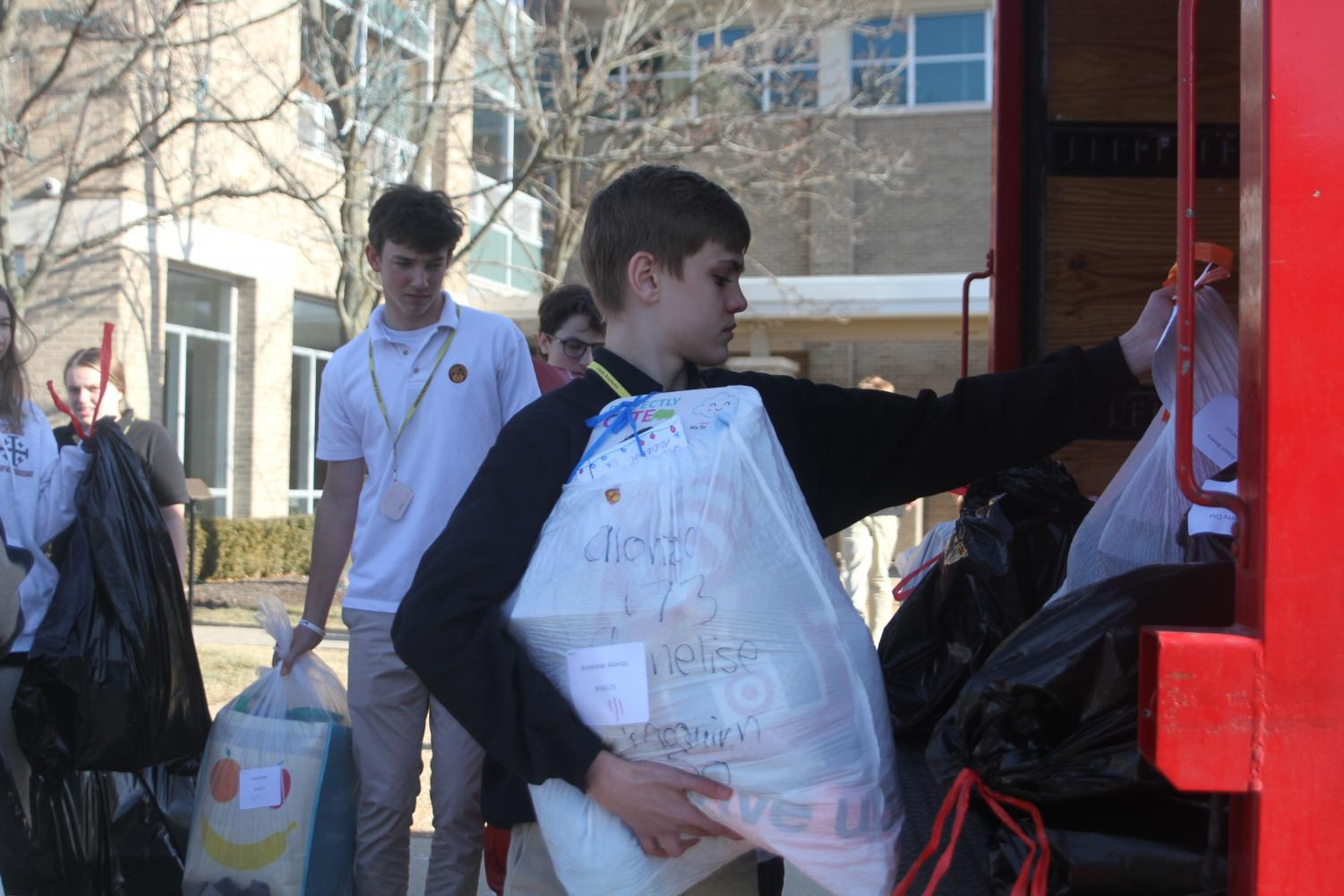 Loyola student places items to be donated to Blessed Virgin Mary families in the delivery truck. The Gonzaga Drive helped 317 families this year.