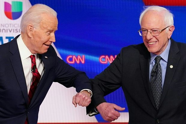 """Biden and Sanders do an """"Elbow Bump"""" before the Democratic Debate on March 15, 2020."""