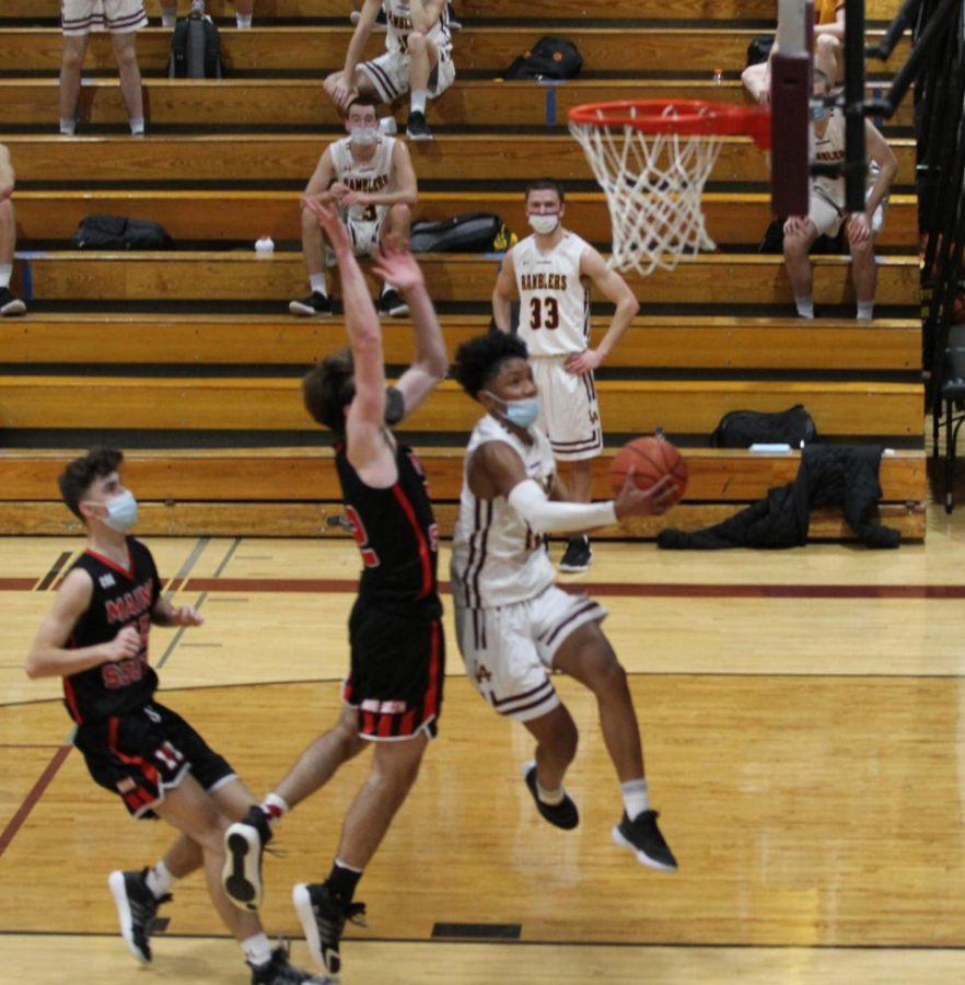 Jalen+Axibal+drives+against+Maine+South.+Despite+a+rough+opening+game%2C+the+Ramblers%27+grit+is+overcoming+their+opponents.+